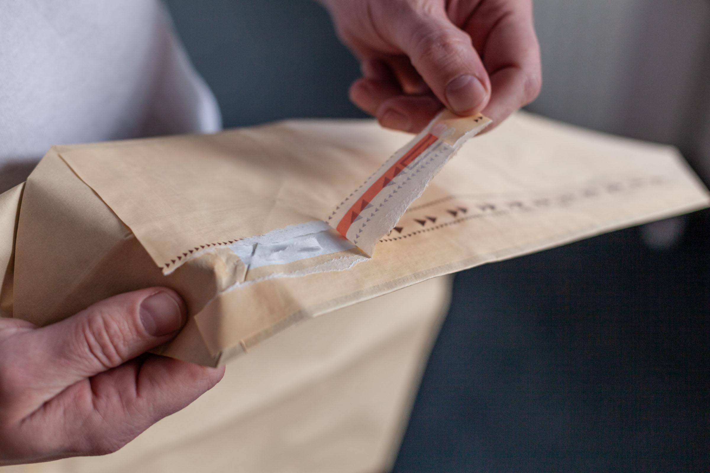 TENAX-Mitarbeiter führt Aufreißfaden an Papiersack vor